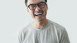 person with glasses on, laughing