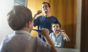A father and son brushing their teeth.