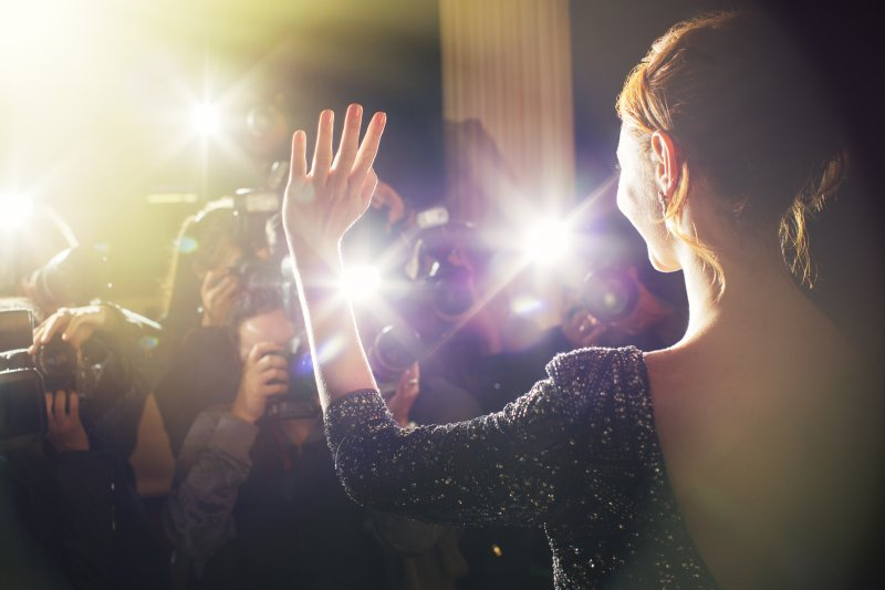 celebrity smiling and waving at paparazzi